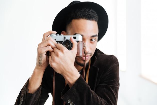 Afrykański mężczyzna robi fotografii na retro kamerze