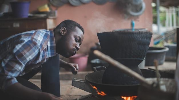 Afrykański mężczyzna siedzi, by dmuchać w ogień i gotować ryż w stylu 16: 9