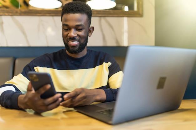 Afrykański mężczyzna siedzi przy stole przy użyciu telefonu siedząc w kawiarni
