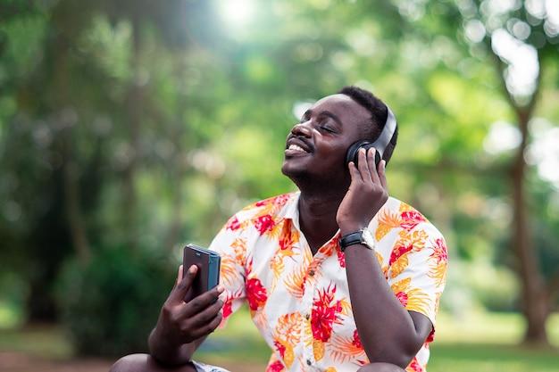 Afrykański mężczyzna słucha muzyka od smartphone z słuchawkami przeciw zielony naturalnemu.