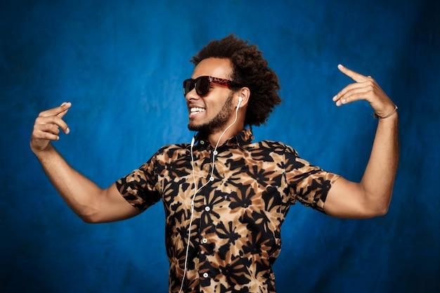 Afrykański mężczyzna słucha muzykę w hełmofonach, tanczy nad błękit ścianą.