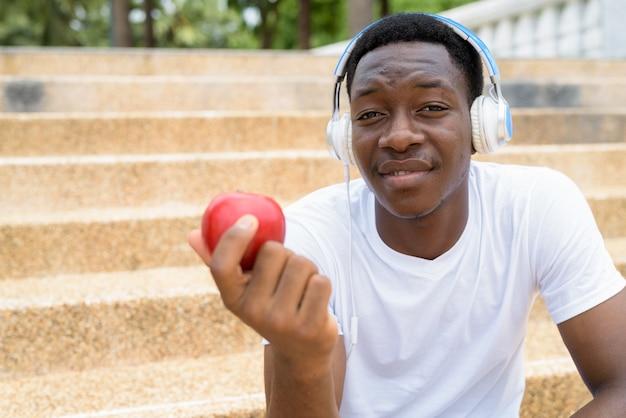 Afrykański mężczyzna słucha muzyki w słuchawkach i trzyma czerwone jabłko