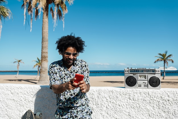 Afrykański mężczyzna słucha muzyki z rocznika stereo boombox na zewnątrz podczas korzystania z telefonu komórkowego - skupić się na twarzy