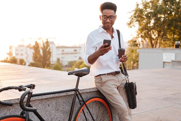 Afrykański mężczyzna stoi blisko bicyklu w wczesnym poranku
