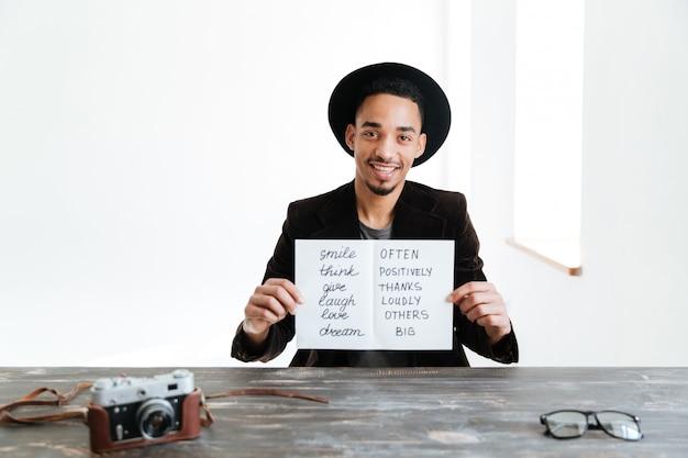 Afrykański mężczyzna trzyma prześcieradło papier z słowami