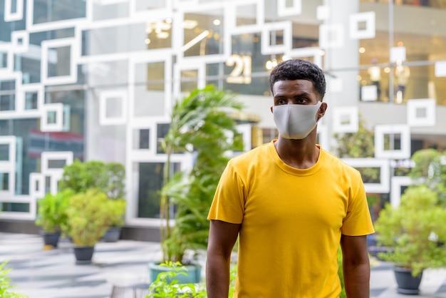 Afrykański mężczyzna ubrany w żółtą koszulkę i maskę na twarz, aby chronić przed koronawirusem covid-19 na zewnątrz w mieście