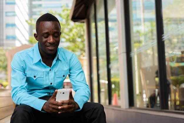 Afrykański mężczyzna uśmiecha się i siedzi podczas korzystania z telefonu komórkowego