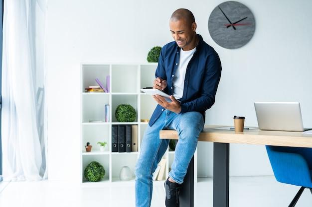 Afrykański mężczyzna używający swojego cyfrowego tabletu siedząc na stole w swoim miejscu pracy