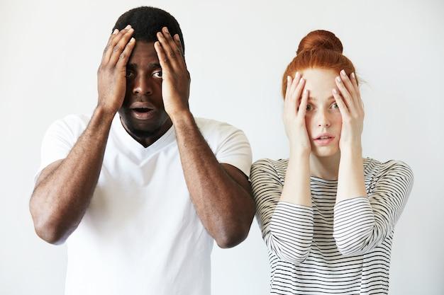Afrykański mężczyzna w białej koszulce i rudowłosy caucasion kobieta w paski w górę