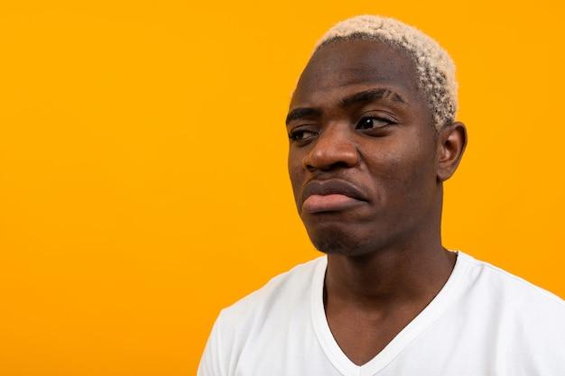 Afrykański mężczyzna w białej koszulce wygląda zaskoczony na żółto z miejsca kopiowania