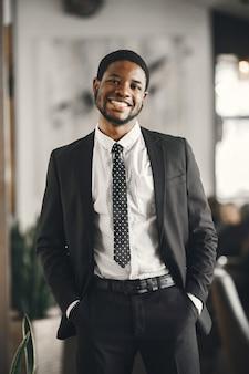 Afrykański mężczyzna w czarnym garniturze.