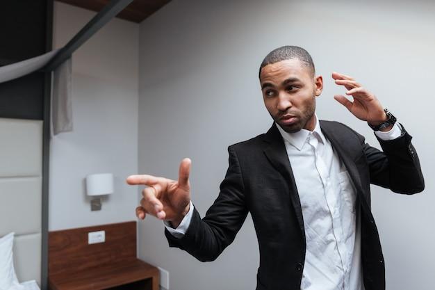 Afrykański mężczyzna w garniturze pozowanie w pokoju hotelowym, wskazując i odwracając wzrok