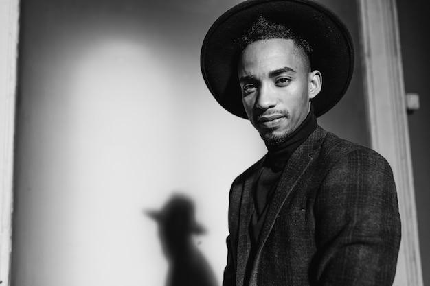 Afrykański mężczyzna w kapeluszu, pozowanie w cieniu. czarno-biały portret dobrego humoru faceta w kurtce.