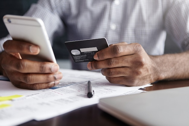 Afrykański mężczyzna w koszuli płaci za towary w internecie przy użyciu karty kredytowej i telefonu komórkowego