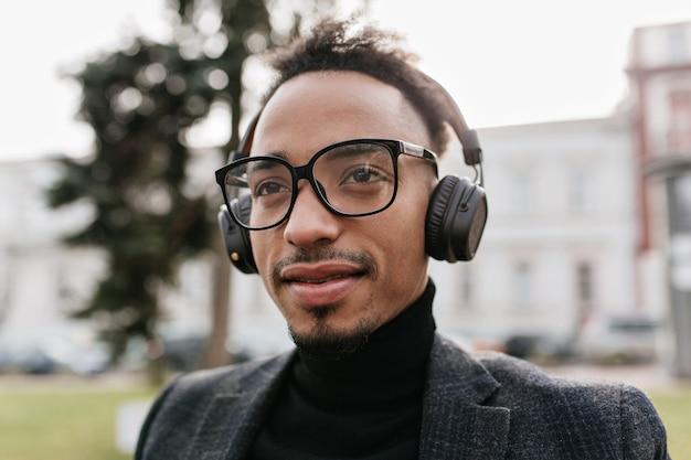 Afrykański mężczyzna w okularach pozuje na miasto z delikatnym uśmiechem. wspaniały czarny brunet odpoczywa na świeżym powietrzu w dużych słuchawkach.