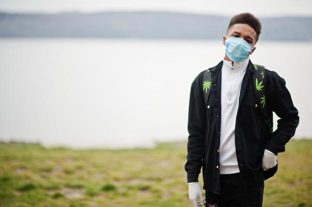 Afrykański mężczyzna w parku w maskach medycznych chroni przed infekcjami i chorobami kwarantanna wirusa koronawirusa.