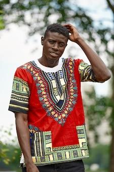 Afrykański mężczyzna w południowoafrykańskich ubraniach krajowych, czarny młody człowiek odpoczywa w parku w krajowych ubraniach.