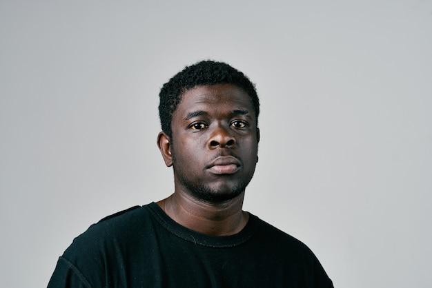 Afrykański mężczyzna w studio mody czarny t-shirt pozowanie zbliżenie. zdjęcie wysokiej jakości