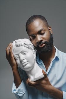 Afrykański mężczyzna w studiu. biała ściana. mężczyzna w niebieskiej koszuli.