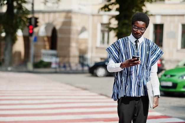 Afrykański mężczyzna w tradycyjnych ubraniach i okularach chodzenie na przejście dla pieszych z telefonem komórkowym i laptopem afryki biznesu.