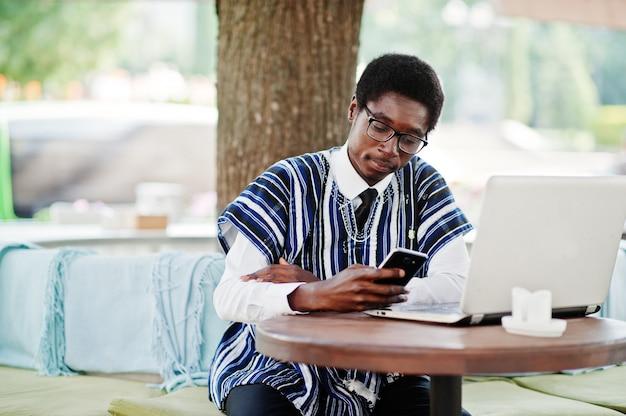 Afrykański mężczyzna w tradycyjnych ubraniach i szkłach siedzi za laptopem przy plenerowym caffe i patrzeje na telefonie komórkowym