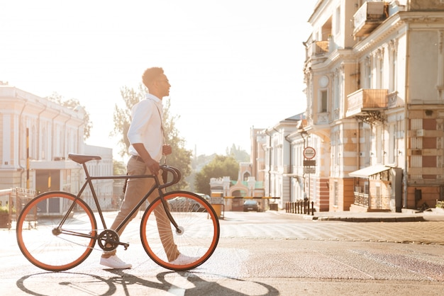 Afrykański mężczyzna wczesny poranek z rowerem chodzi outdoors