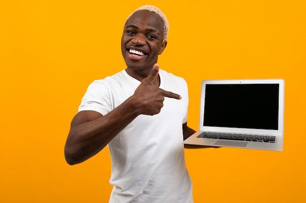 Afrykański mężczyzna wskazuje mienie ekran laptopu z białym włosy uśmiechniętym ekranem naprzód z układem ekranizuje na kolorze żółtym