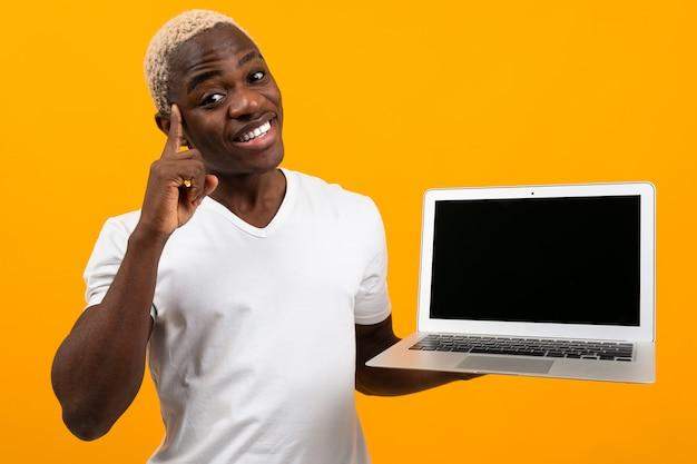 Afrykański mężczyzna z białego włosy uśmiechniętym mienie laptopu ekranem naprzód na kolorze żółtym