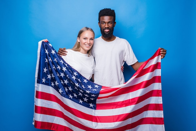 Afrykański mężczyzna z kaukaską kobietą trzymającą amerykańską flagę odizolowaną na niebieskiej ścianie