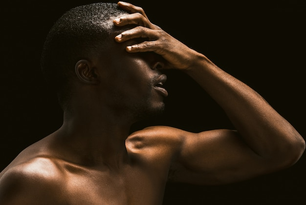 Afrykański mężczyzna zakrył twarz dłonią, widok profilu nagiego amerykanina afrykańskiego pochodzenia młodego faceta pozuje na czarnym tle