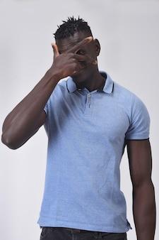 Afrykański mężczyzna zerkanie z ręką na twarzy na białym tle