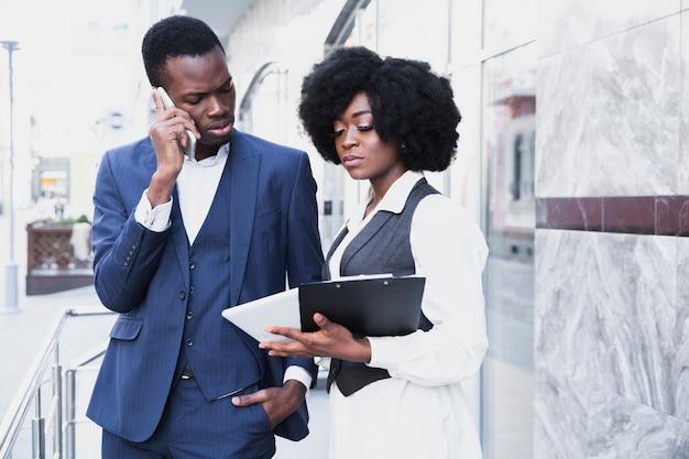 Afrykański młody biznesmen opowiada na telefonie komórkowym patrzeje cyfrowego pastylka chwyt jego kolega