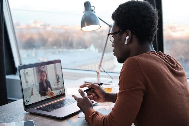 Afrykański młody biznesmen rozmawia ze swoim kolegą online za pomocą laptopa podczas pracy w biurze
