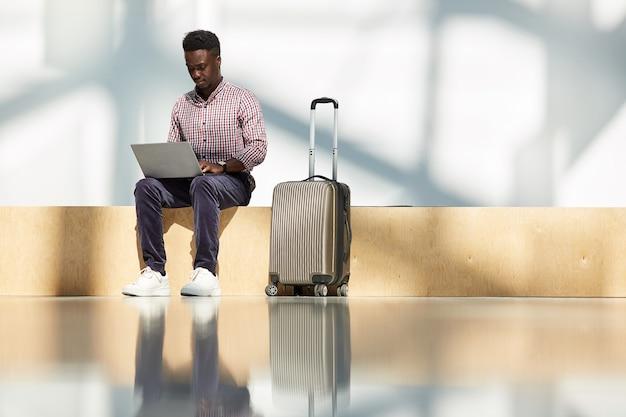 Afrykański młody biznesmen siedzi na lotnisku z bagażem i pracuje na laptopie, czekając na swój lot