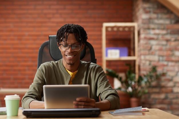 Afrykański młody biznesmen siedział przy stole i pracując online na cyfrowym tablecie w biurze on wpisując i uśmiechając się