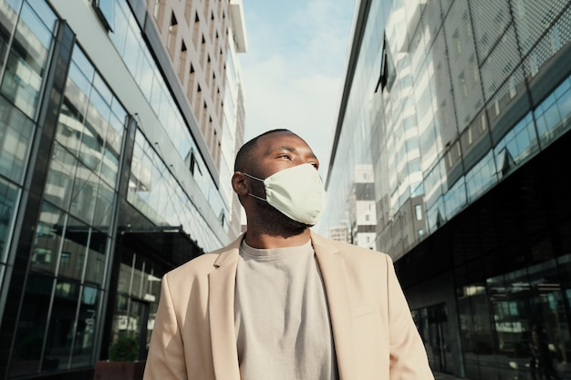 Afrykański młody biznesmen w masce ochronnej stojącej w mieście z nowoczesnymi budynkami w tle