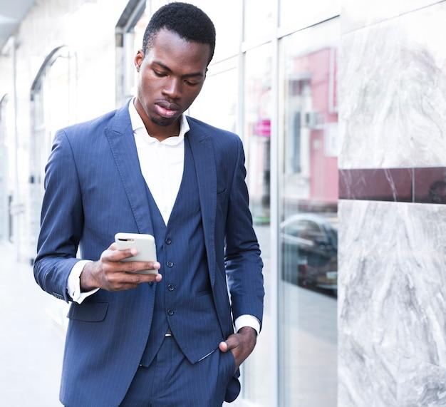 Afrykański młody biznesmen z rękami w kieszeni za pomocą telefonu komórkowego