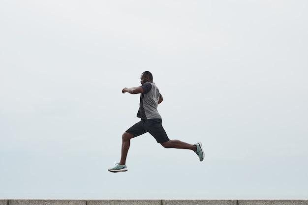 Afrykański młody człowiek ćwiczący na świeżym powietrzu przeskakuje przez barierę