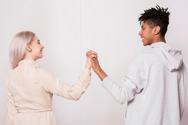 Afrykański młody człowiek i blondynki kobieta trzyma nawzajem ręki stoi przeciw białemu tłu