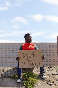 Afrykański młody człowiek siedzi na kamieniu i trzymając w rękach afisz, chroni naturę