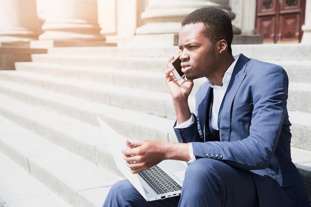 Afrykański młody człowiek siedzi na schody trzymając laptopa rozmawiać na telefon komórkowy