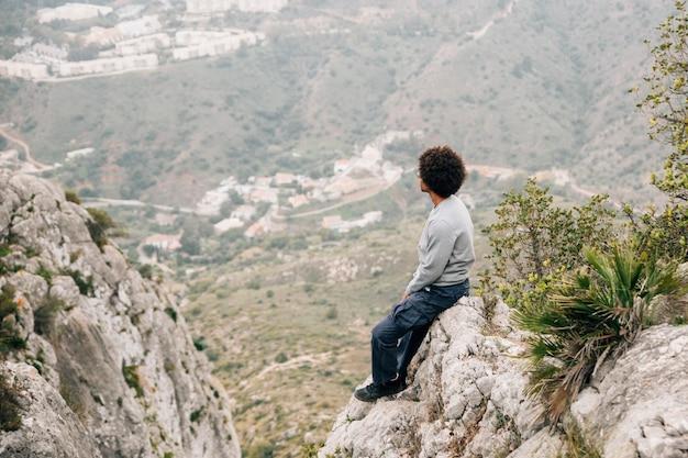 Afrykański młody człowiek siedzi na skale z widokiem na góry