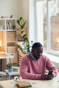Afrykański młody człowiek siedzi przy stole w biurze, wpisując wiadomość w swoim telefonie komórkowym
