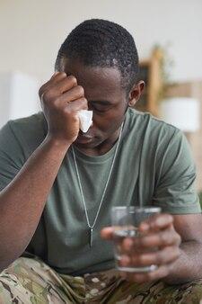 Afrykański młody człowiek siedzi w depresji ze szklanką wody