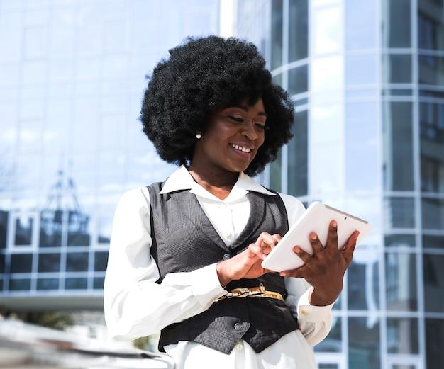 Afrykański młody człowiek używa cyfrową pastylkę przed korporacyjnym budynkiem