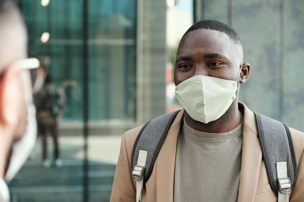 Afrykański młody człowiek w masce ochronnej rozmawia ze swoim kolegą stojąc w mieście