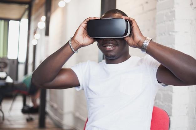 Afrykański młody człowiek w okularach wirtualnej rzeczywistości w nowoczesnym wnętrzu coworking studio. smartfon korzystający z gogli vr.