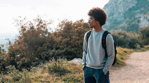 Afrykański młody człowiek z rękami w kieszeni patrzeje widok