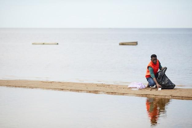 Afrykański młody człowiek zbiera śmieci do worków, sprzątając brzeg rzeki na zewnątrz