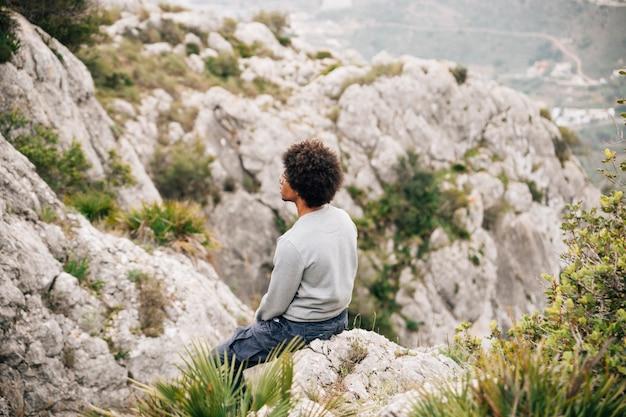 Afrykański młody męski wycieczkowicz siedzi na skalistej górze